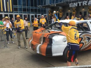 A father and son takes swings at the Ducks car on the plaza before Game 3. (Photo credit: ESPN 102.5 The Game / Ryan Porth)