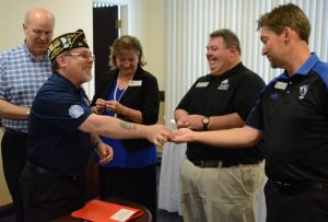 Christopher Benigno, chairman of American Legion Illinois Premier Boys State, gave EIU staff members an Illinois Premiere Boys State lapel pin after signing a 10-year contract extension. Shown, from left to right, are Mark Hudson; Lynette Drake, interim vice president for students affairs; Matt Boyer, assistant director, Residential Life and Conference Services; and Jody Stone, senior associate director, University Housing and Dining Services.