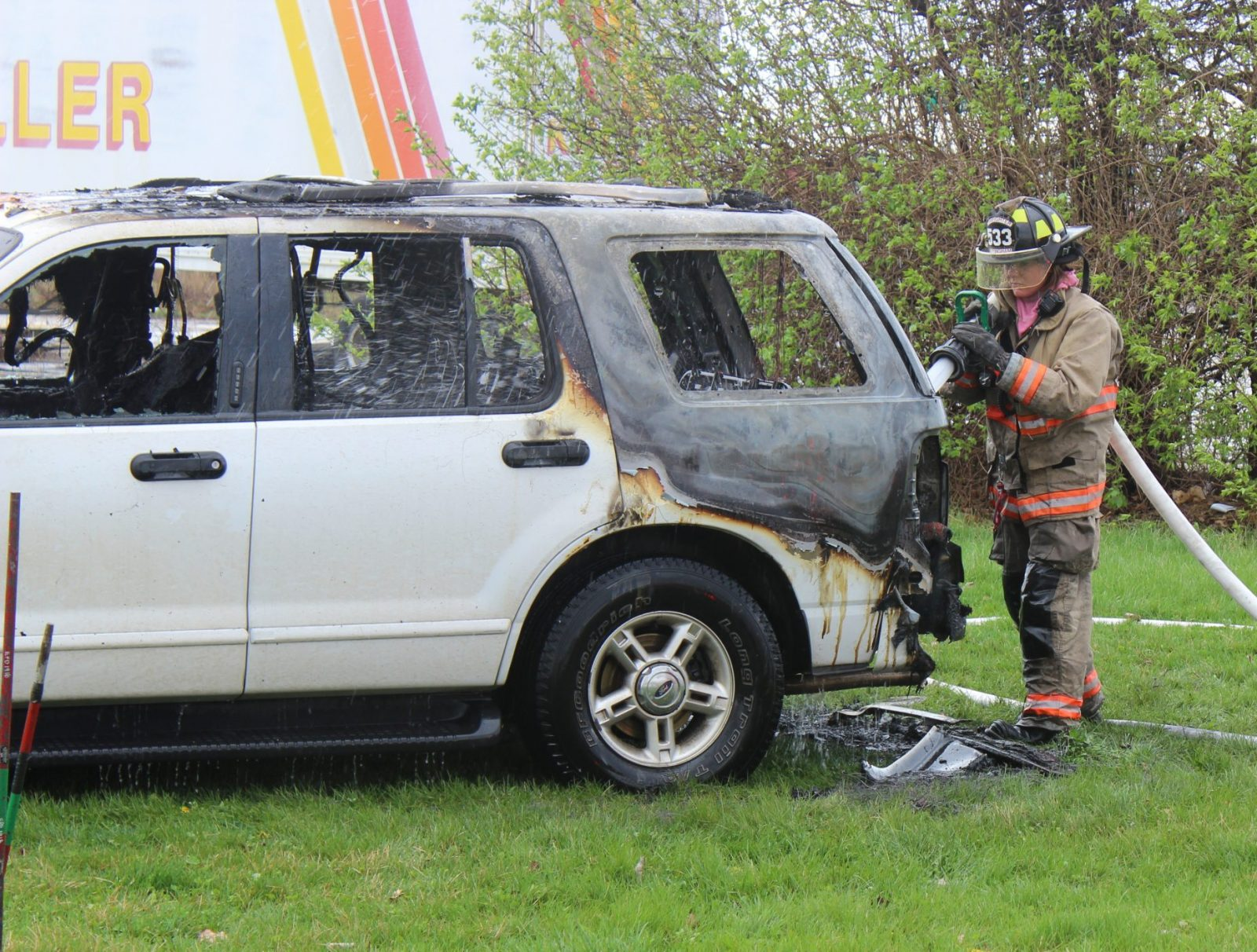 An Effingham Fire Fighter extinguishes the rear-interior of a Ford Explorer that was on fire earlier.