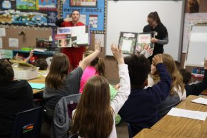 Ms. Davis's third graders at Charleston's Carl Sandburg School eagerly raise their hands for the opportunity to show off their dental knowledge to Lake Land College Dental Hygiene students Fallon Sullivan and Laura Koester.