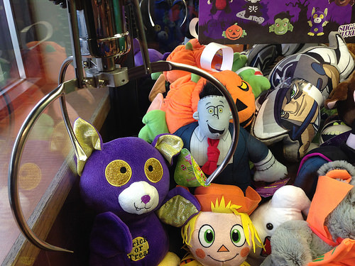A Woman Squeezes Through a Tiny Slot in a Claw Game to Steal Seven Stuffed Animals