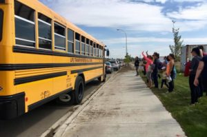 Parents wave to students after their first ride alone on the school bus Aug. 22, 2017. (Jessie Anton/980 CJME)