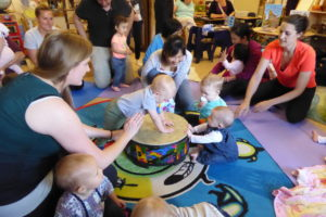 Babies play the drum at Early Years Family Centre