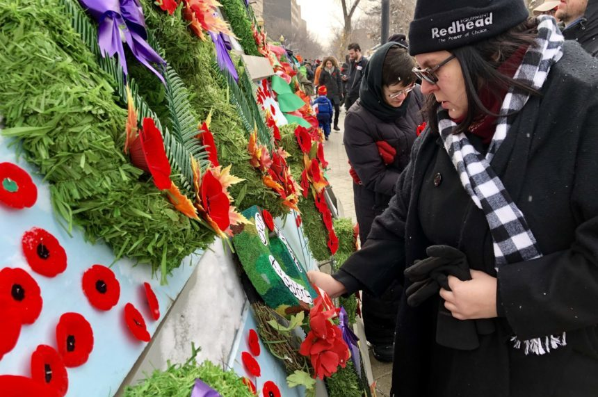 People pin their poppies on the Victoria Park Cenotaph after Regina's outdoor Remembrance Day service Nov. 11, 2017. (Jessie Anton/980 CJME)