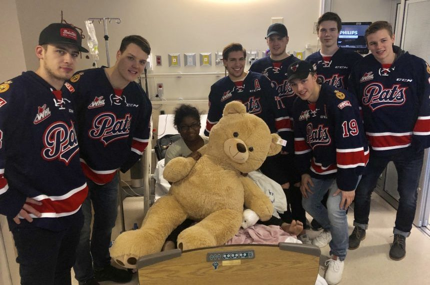 Regina Pats players deliver teddy bears from on-ice toss
