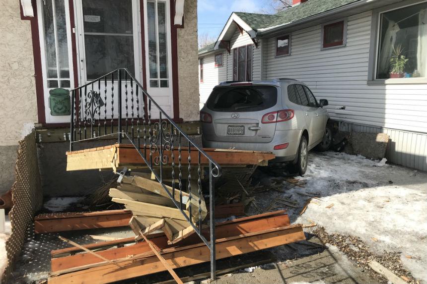SUV gets wedged between 2 homes, woman in hospital