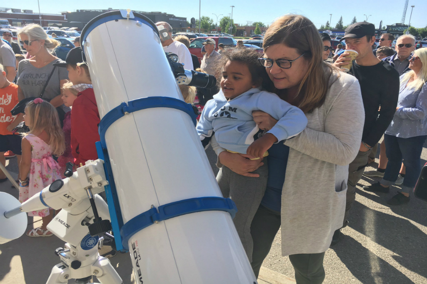Heather Kirkpatrick and her granddaughter look through one of eight telescopes at setup at London Drugs on 8th street in Saskatoon to see a partial solar eclipse on Aug. 21, 2017. (JT Marshall/650 CKOM)