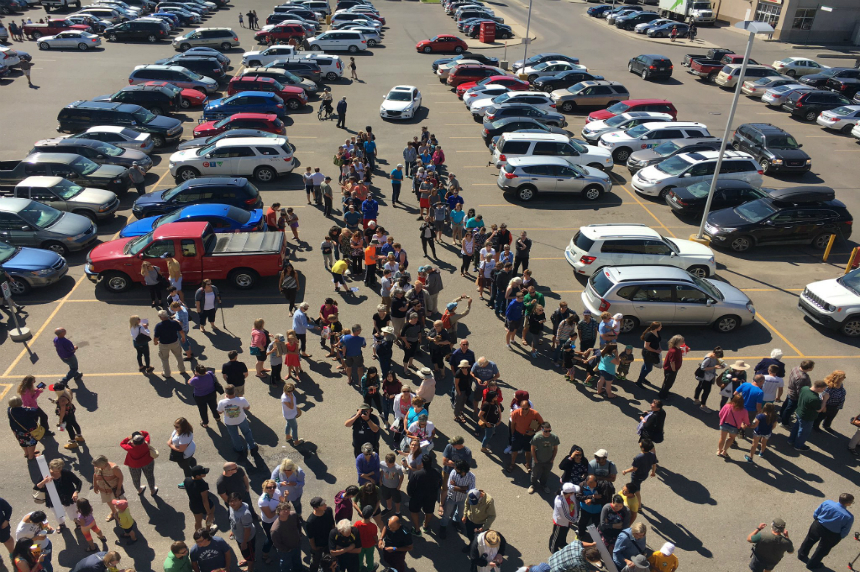 Hundreds of people gather at the London Drugs on 8th street in Saskatoon to view a partial solar eclipse on Aug. 21, 2017. (JT Marshall/650 CKOM)