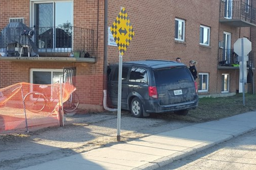Update: Man arrested after minivan crashes into apartment building