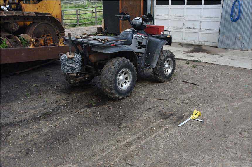 Witnesses say either Cassidy Cross or Eric Meechance attempted to start a quad sitting near a work shed on Gerald Stanley's farm. An evidence placard marks where a damaged wheel rim on the grey SUV Colten Boushie was in began reversing when the confrontation began. (RCMP)