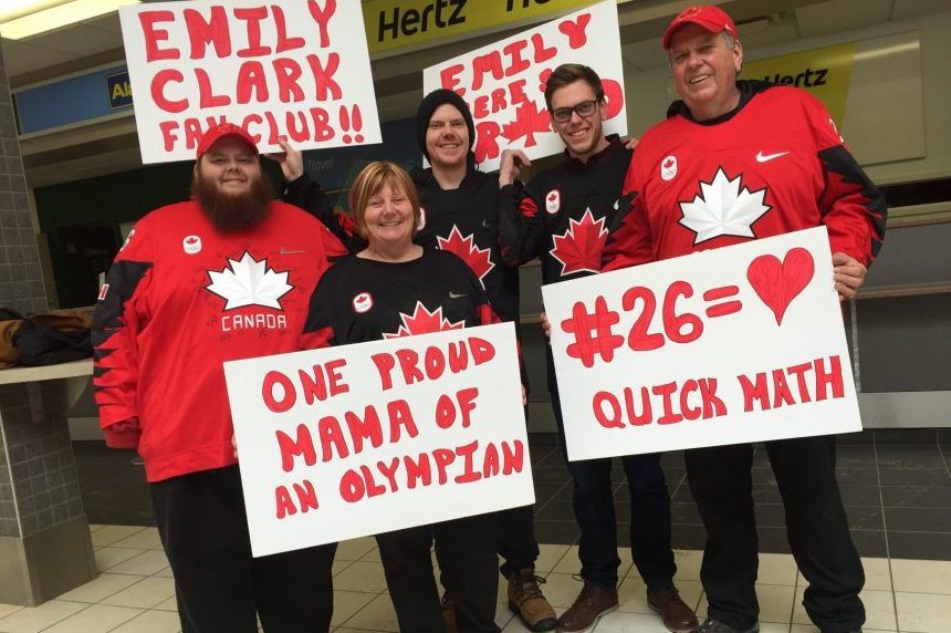Emily Clark's family holds signs welcoming the Olympian home at the Saskatoon airport on Feb. 27, 2018. (Daniella Ponticelli/650 CKOM)