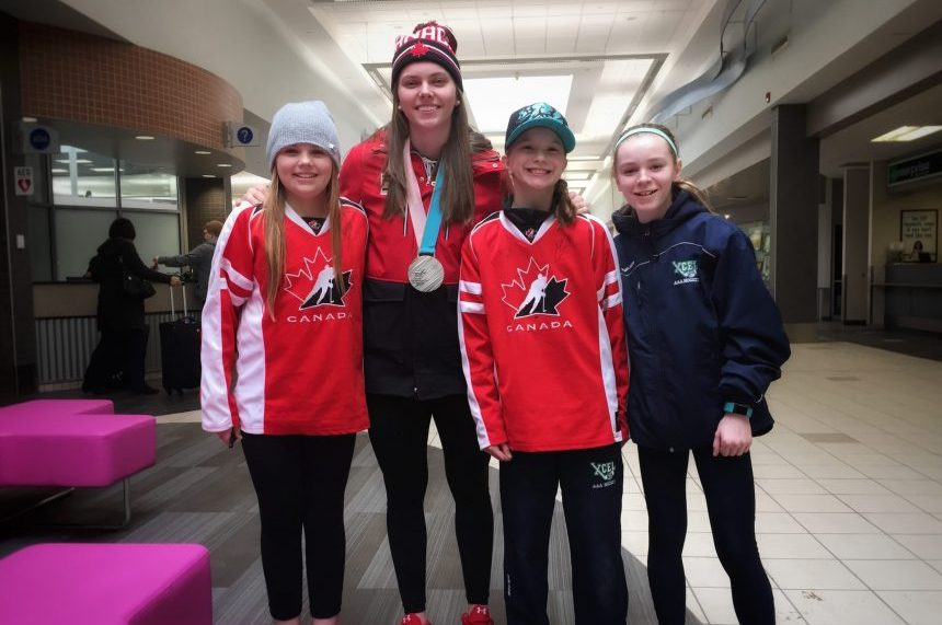 Olympian Emily Clark poses with minor hockey players Sage, Ireland and Bree, after arriving at the Saskatoon airport on Feb. 27, 2018. (Daniella Ponticelli/650 CKOM)