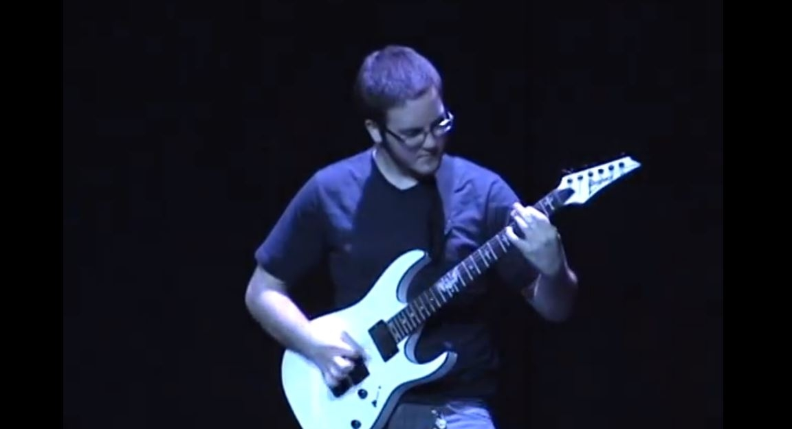Kid crushes complex heavy metal solo at talent show.